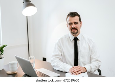 Portrait of bearded senior businessman at his workplace