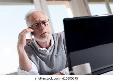 Portrait of bearded senior businessman talking on mobile phone in office, hard light