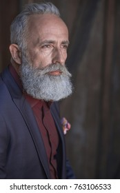Portrait of bearded senior demonstrating seriousness in room. Occupation concept