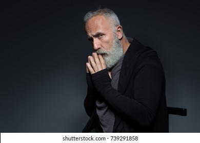 Portrait of bearded senior male dressed in a stylish clothes sitting on the chair looking seriously at camera