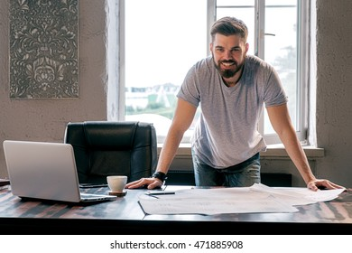 Portrait of bearded smiling businessman at desk with drawings,laptop and coffee cup looking at camera