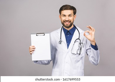 Portrait of bearded smiling intern, who is holding the clipboard with empty paper. Doctor is wearing white uniform, stands over isolated grey background, showing blank.