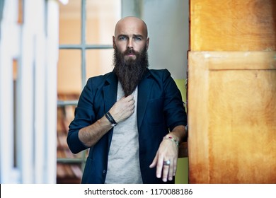 Portrait of bearded thoughtful man strokes beard. Confident concept