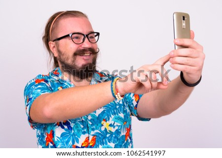 f0b045d75 Portrait of bearded tourist man with mustache and long hair wearing  Hawaiian shirt against white background