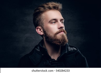 Portrait of a bearded urban male isolated with contrast illumination on grey vignette background.