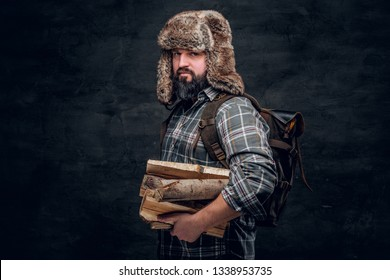 Portrait of a bearded woodcutter with a backpack dressed in a plaid shirt and trapper hat holding firewood. Studio photo against a dark textured wall