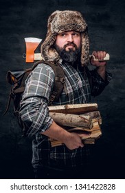 Portrait of a bearded woodcutter with a backpack dressed in a plaid shirt and trapper hat holding firewood and ax. Studio photo against a dark textured wall