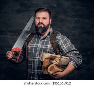 Portrait of a bearded woodcutter with a backpack dressed in a plaid shirt holding firewood and hand saw. Studio photo against a dark textured wall