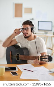 Portrait of bearded young composer in eyeglasses playing on guitar and composing a song at the table