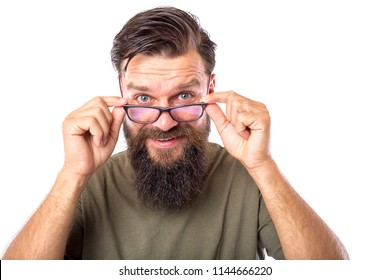 Portrait of bearded young man adjusting his glasses and looking at camera while standing against white background