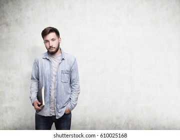 Portrait of a bearded young man wearinig a jeans shirt holding a blue notebook and standing near a concrete wall. Mock up.
