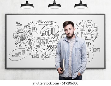 Portrait of a bearded young man wearinig a jeans shirt holding a blue notebook and standing near a whiteboard with a business plan sketch.