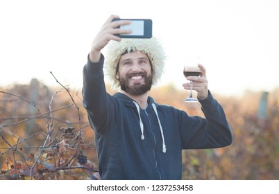 Portrait of beardman with wine glass wearing traditional georgian shepherd's hat. Man in Papakha. Glass of red wine in hand, the young winemakers in the vineyard. Make selfie.