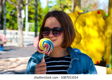 Portrait beauiful brunette woman with lollipop in park.