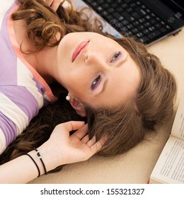 Portrait of a beautful girl who is reading a book while lying on the floor