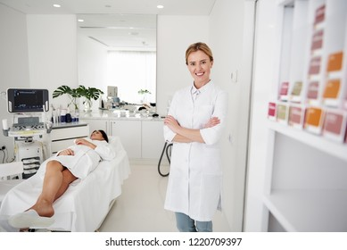Portrait of beautician in white lab coat looking at camera and smiling while brunette woman in bathrobe lying on daybed