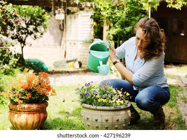 Portrait of beautiful 40 years old woman gardening on sunny day in the garden