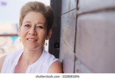Portrait of beautiful 45 years old woman walking on seaside