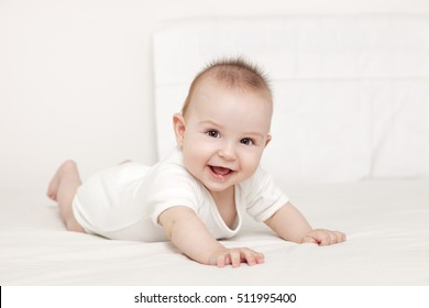 Portrait of a beautiful 6 months baby smiling, on white background