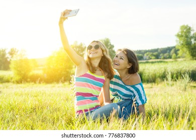 Portrait of beautiful adult mother and her daughter teenage girl making a selfie using a smart phone and smiling.