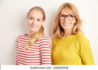 Portrait of beautiful adult woman and her attractive youthful mother standing togethter at isolated white background with copy space.