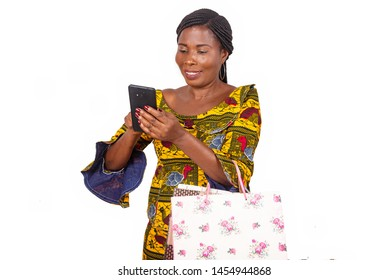 Portrait of beautiful african adult woman holding colorful paper bags looking at a message or videos on her mobile phone isolated on white background