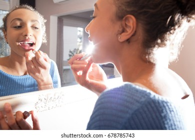 Portrait of beautiful african american adolescent young woman looking at herself in mirror applying lipstick make up, home interior. Black female teenager using cosmetics with light flare, indoors.