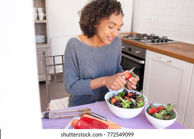 Portrait of a beautiful african american adolescent girl preparing salad, slicing eating fruit and vegetables in home kitchen, smiling indoors. Young black woman cooking healthy vegan food, lifestyle.
