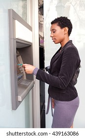 Portrait of beautiful african american business woman using a credit card in a bank cash point in the city, outdoors lifestyle. Smiling professional ethnic woman accessing funds in slick bank.