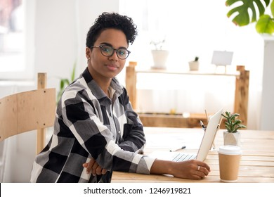 Portrait of beautiful African American female in glasses working at laptop in loft office, smiling black woman look at camera posing at cozy workplace, mixed race girl sit at desk using computer