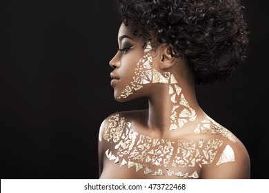Portrait of beautiful African American girl with dark curly hair. Nice make-up, hairdo. Covered with golden patterns. Turned aside, profile. Head and shoulders, profile, indoors, studio
