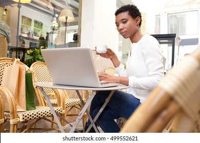 Portrait of beautiful african american professional woman sitting in coffee shop using a laptop computer, working outdoors. Smart black business woman in city, thoughtful drinking coffee in exterior.