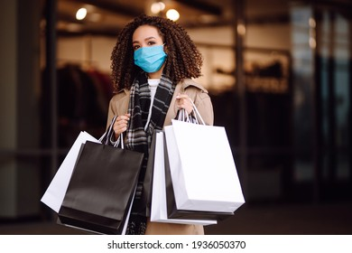 Portrait of beautiful african american woman in protective medical mask after shopping near the store. Shopping during the coronavirus Covid-19 pandemic. Sales And Discount, Retail, Purchase.