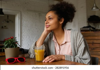 Portrait of a beautiful african american woman sitting at home thinking