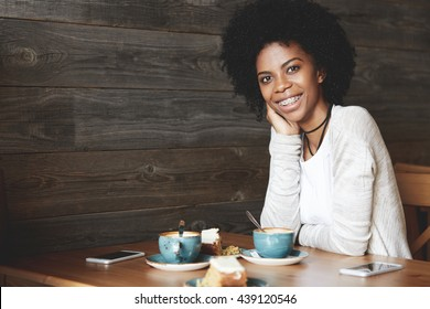 Portrait of beautiful African American woman with Afro haircut wearing trendy clothes, looking and smiling at the camera, showing white teeth with braces, leaning her elbow on the wooden table