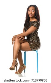 Portrait of beautiful African American woman in elegant dress seated on chair isolated over white background