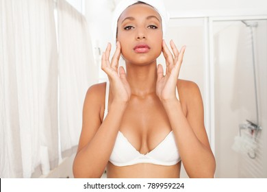 Portrait of beautiful african american young woman getting ready in home bathroom applying face cream cosmetics, looking in interior. Black female in lingerie, body care, healthy well being lifestyle.