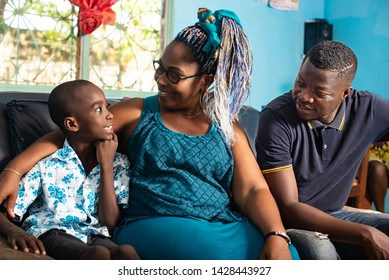 portrait of a beautiful African family sitting comfortably together on the couch talking with their cute little gracon