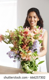 Portrait of beautiful african girl smiling looking at camera holding bouquet of alstroemerias.
