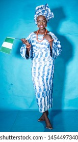Portrait of a beautiful African woman dressed in Yoruba traditional attire and waving the Nigerian flag