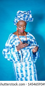 Portrait of beautiful African woman making a payment with her credit card and mobile phone