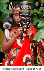 Portrait of a beautiful African woman wearing traditional clothing sitting outside with foliage in the background holding a mask in front of her face