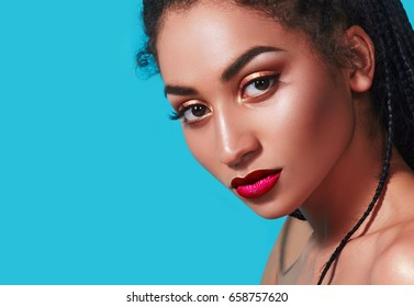 Portrait of a beautiful African-American girl with braided pigtails on a bright blue background. Dark smooth skin. Long eyelashes, brown eyes. The Negress.