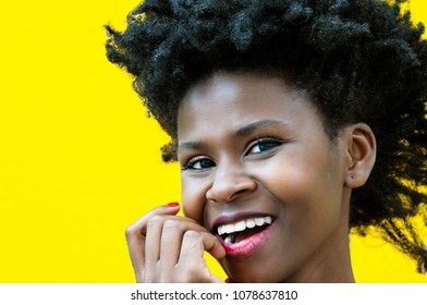 Portrait of a beautiful afro american young woman smiling on a yellow background