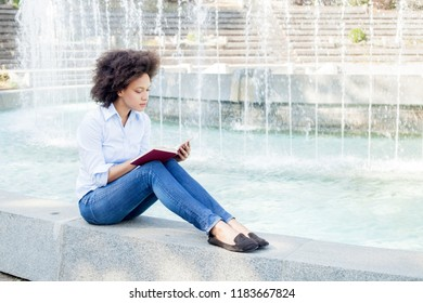 Portrait of Beautiful Afro American Young Woman Reading The Book, attractive mixed race female relaxing outdoor, casual wear
