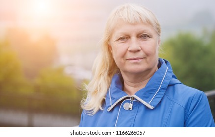 Portrait of beautiful aged woman in the street. With sunlight effect.