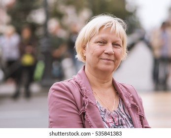 Portrait of beautiful aged woman in the street. Selective soft focus on eyes.