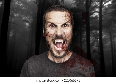 portrait of a beautiful angry male vampire on a dark forest background