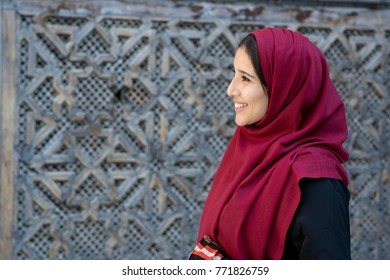 Portrait of beautiful Arab woman in traditional clothing with red hijab in traditional ambient