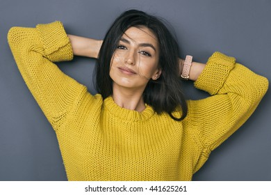 Portrait of beautiful Armenian girl with arms behind head smiling at camera against of grey wall.